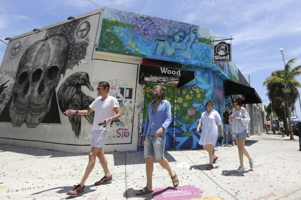 Visitors stroll through the Wynwood area Friday in Miami. Florida now reports 21 people have contracted the Zika virus in a 1-square-mile area encompassing Wynwood.