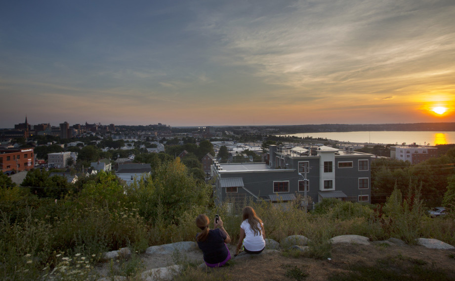 Nicole Hoglund of Portland, left, watches the sunset with her niece Sophia Lanzano of New Jersey on Thursday from Fort Sumner Park in Portland. The top floor of a proposed condominium complex would obscure this view of Back Cove.