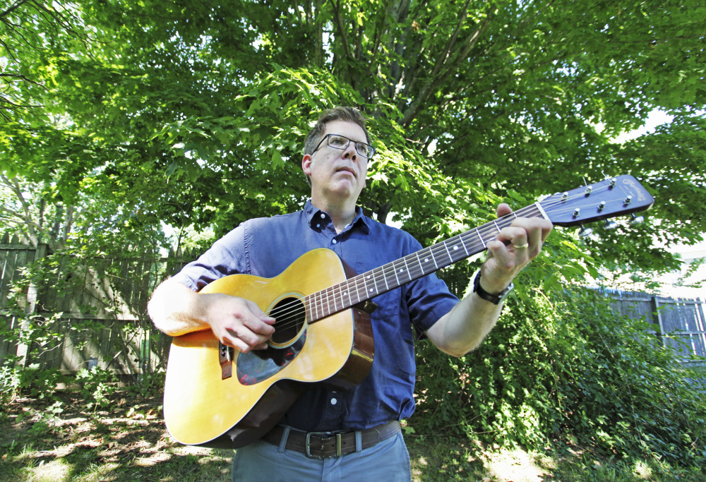 Jason Crigler plays his 1964 Martin 00-18 at home in South Berwick. (Photos by Jill Brady/Staff Photographer)