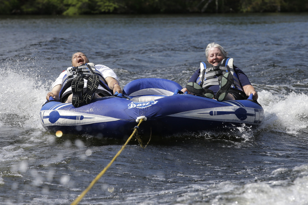 Navy veteran Raquel Ardin of North Hartland, Vt., left, who suffered a broken neck while serving in the Navy, laughs while riding an inflatable craft with her partner Lynda Deforge, right, also of North Hartland, during a rehabilitation clinic in Coventry, R.I.