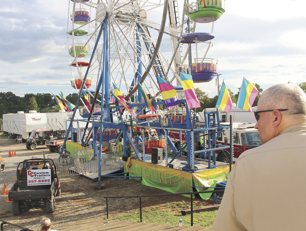 Baileyton, Tenn., police Officer Kenneth Bitner watches as the area is cordoned off after three girls fell from the Ferris wheel at a county fair in Greenville, Tenn. Police say one of the girls suffered a traumatic head injury and remains hospitalized in serious condition.