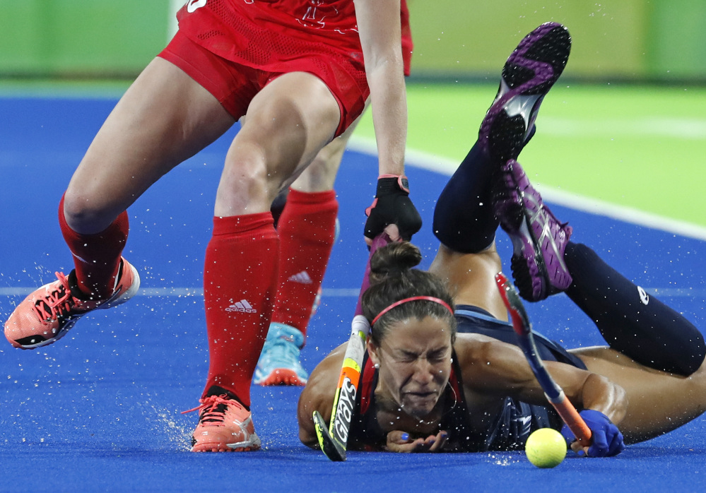 Melissa Gonzalez of the U.S. falls while fighting for the ball with Britain's Nicola White during a field hockey preliminary-round match Saturday. The U.S. suffered its first loss of the tournament, 2-1.
