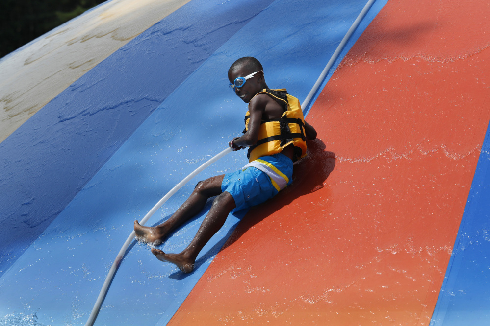 Noah Pacheco, 11, of New York City slides down the Aquasaucer slide Sunday at Aquaboggan Water Park in Saco. This is Noah's first year with his host family and as well as his first time away from New York City.