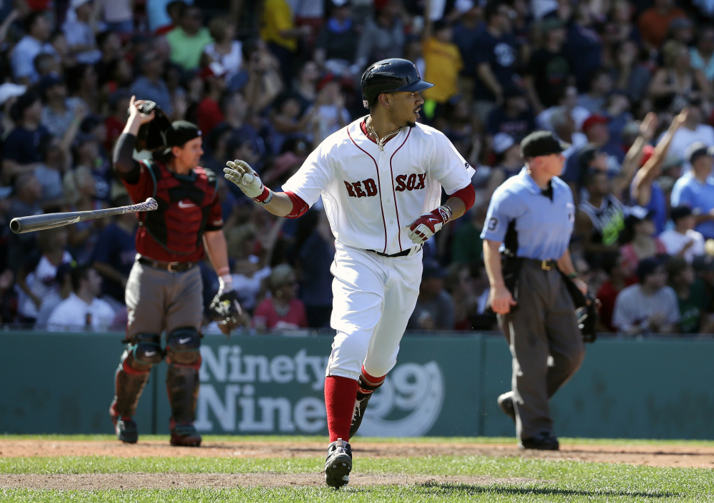 Boston's Mookie Betts watches the flight of his three-run home run as Arizona Diamondbacks' Tuffy Gosewisch looks on in the fifth inning Sunday at Fenway Park.