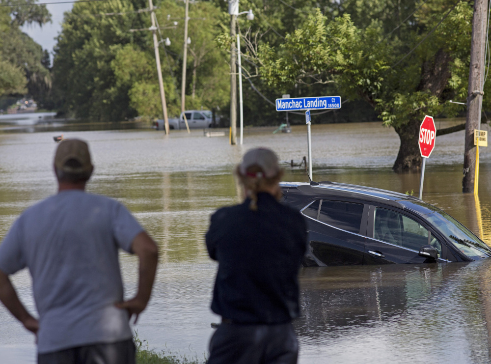 """Residents survey the floodwater near Prairieville, La., Tuesday.  Gov. John Bel Edwards told a news briefing, """"I don't know that we have a good handle on the number of people who are missing."""""""