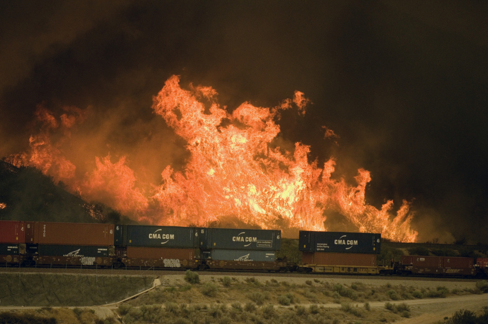 Flames erupt on a hillside alongside one of the main rail routes connecting Southern California with points north and east as a wildfire rages out of control in Cajon Pass north of Devore.