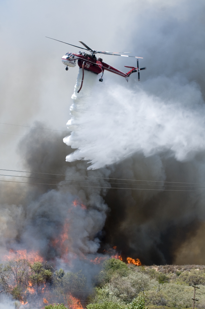 A helicopter makes a water drop on a wildfire as it burns near Cleghorn Road in the Cajon Pass in California. The fire forced the shutdown of a section of Interstate 15, the main highway between Los Angeles and Las Vegas, leaving commuters stranded for hours.