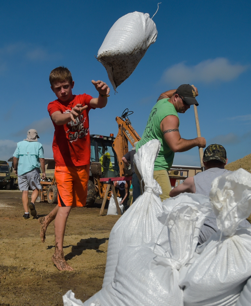A child piles sandbags to stop rising floodwaters in Lake Arthur, La., on Wednesday. Most people in the area lack flood insurance and many are living amid mud and the threat of mold.