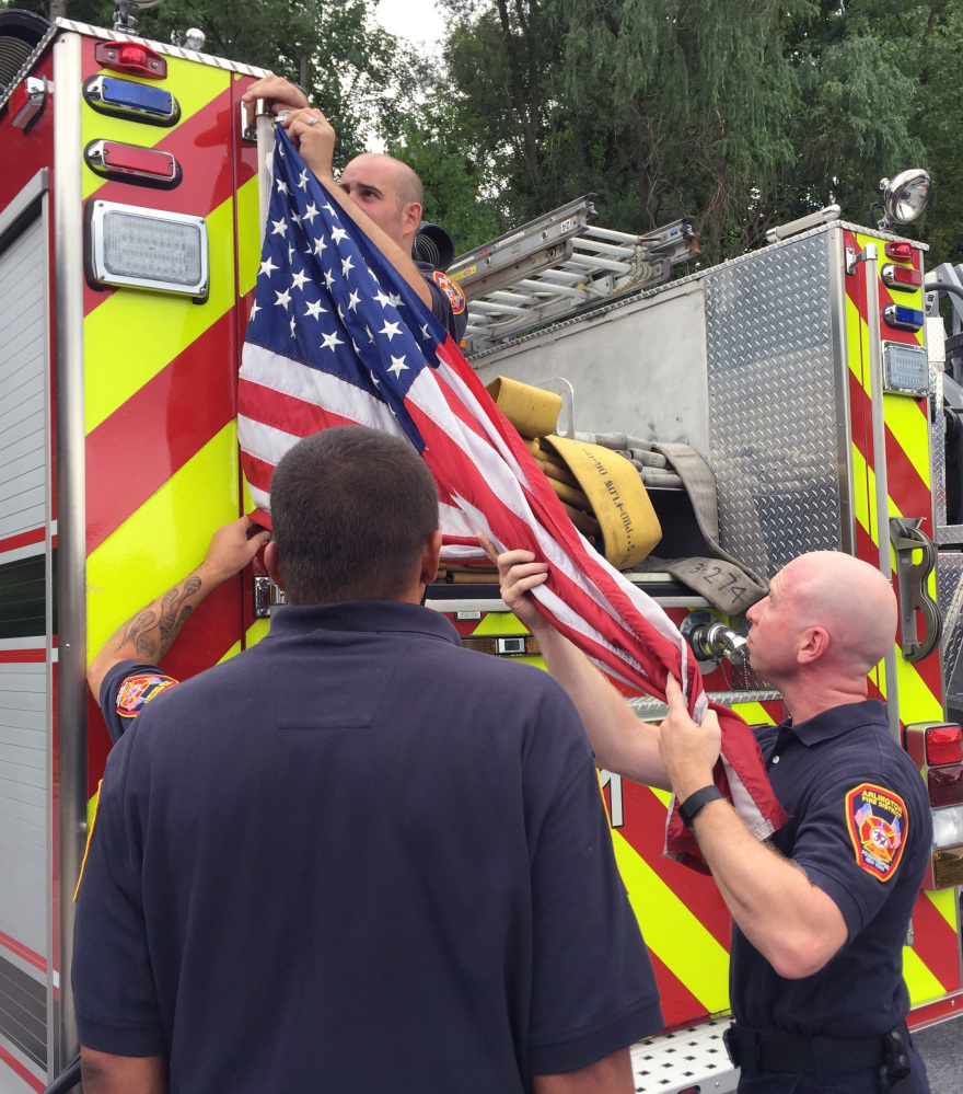 Firefighters remove the banners Tuesday in the Arlington Fire District of Poughkeepsie, N.Y.