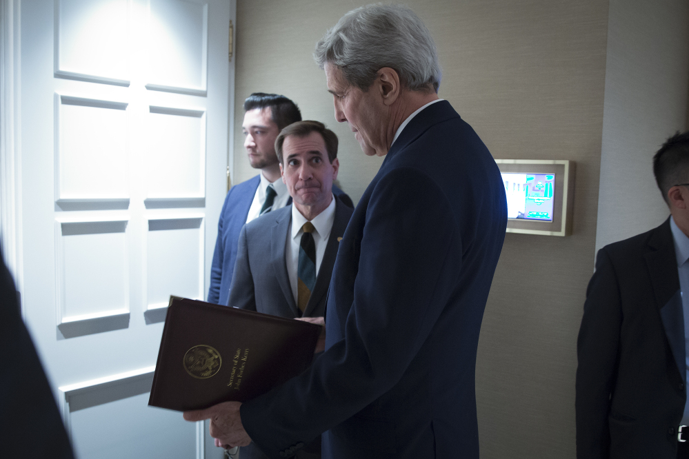 Secretary of State John Kerry speaks to senior adviser John Kirby last year in Vienna. Kirby says negotiations over the U.S. returning Iranian money from a decades-old account was conducted separately from talks that resulted in the release of Americans from Iran.