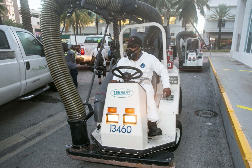 A City of Miami Beach Sanitation worker gets ready to clean the alleyways of South Beach, sucking up still waters and debris with a mobile vacuum, Friday, Aug. 19, 2016, Miami Beach, Fla., as part of the city's Zika prevention clean-up programs.