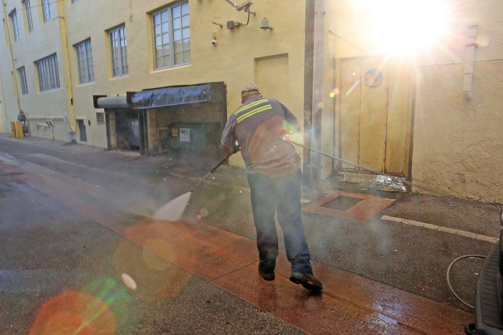 Melvin Gaitan of the Miami Beach Sanitation Department washes an alley Friday with a high pressure water machine that is set to 250 degrees Fahrenheit, which kills any bacteria or mosquito larvae that could be growing in still waters.