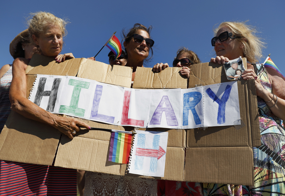 """The four """"Smith Sisters"""" from New York state hold a sign they made supporting Democratic presidential candidate Hillary Clinton outside the gate of Provincetown Municipal Airport in Provincetown, Mass."""