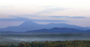 Early morning haze colors Mount Katahdin and its surrounding mountains in this view from land along Route 11 in Patten. Roxanne Quimby's efforts to bring a national monument to the area have added to the debate over the changing use of Maine's vast forestlands.