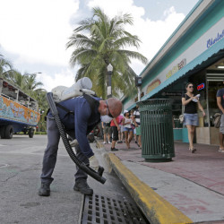 "Miami-Dade mosquito control inspector Yasser ""Jazz"" Compagines sprays a chemical mist into a storm drain Tuesday as a tour vessel passes by in Miami Beach. Bermuda, among other places, is seeing an uptick in visitors."