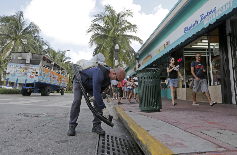 """Miami-Dade mosquito control inspector Yasser """"Jazz"""" Compagines sprays a chemical mist into a storm drain Tuesday as a tour vessel passes by in Miami Beach. Bermuda, among other places, is seeing an uptick in visitors."""