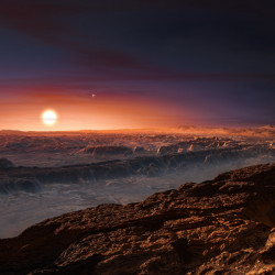 This artist rendering depicts a view of the surface of the planet Proxima b orbiting the red dwarf star Proxima Centauri, the closest star to our solar system. The double star Alpha Centauri AB also appears in the image to the upper-right of Proxima itself.