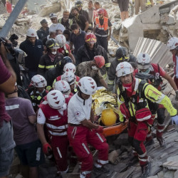 A survivor is pulled out in Amatrice, Italy, where an earthquake struck just after 3:30 a.m., Wednesday. Left: People hug next to a collapsed house after the quake hit Pescara del Tronto. The number of dead and missing is uncertain.