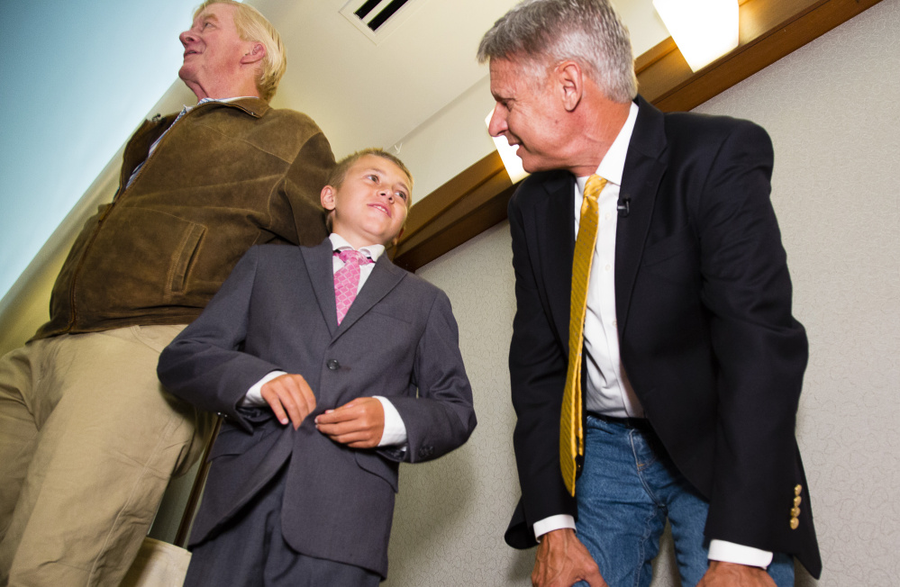 Former New Mexico Gov. Gary Johnson talks with Tristian Pelletier, 12, of Bethel at the Portland Regency on Friday as he campaigns with former Massachusetts Gov. Bill Weld, left.
