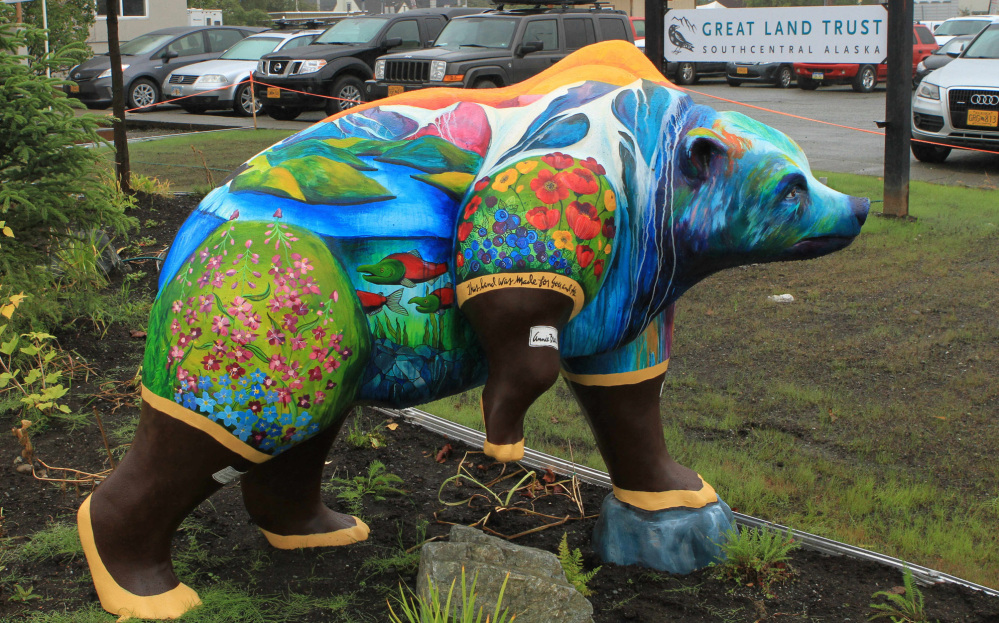 Nature scenes and rubber boots adorn this faux grizzly in front of offices of Great Land Trust.