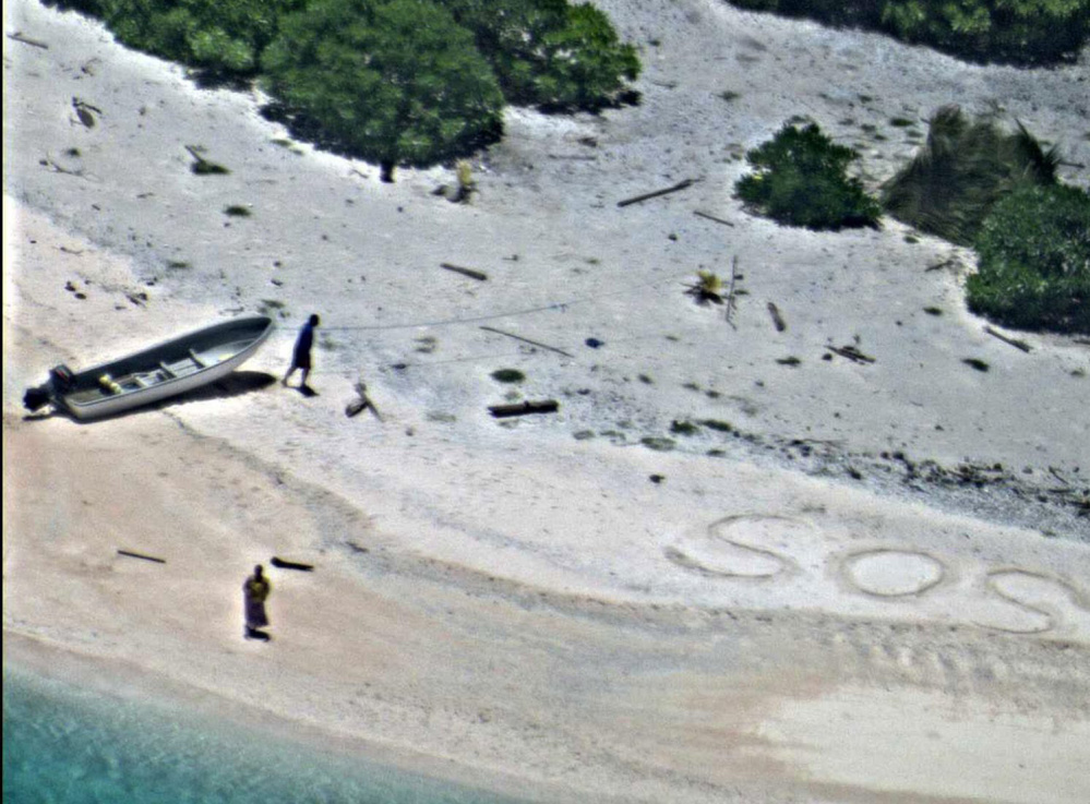 """Two stranded mariners signal for help with an """"SOS"""" in the sand as a Navy P-8A Poseidon aircraft crew flies over as part of a Coast Guard search of the Pacific on Wednesday."""