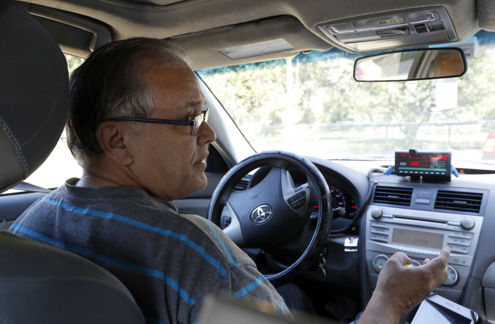 Taxi driver Luis Rosado speaks to a reporter while stopped at a red light in New York City.