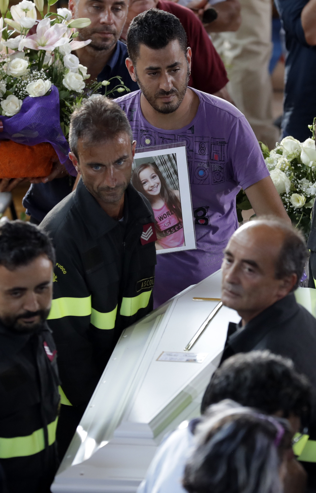 The coffin of 9-year-old Giulia Rinaldo is carried outside a gymnasium at the end of the state funeral service for earthquake victims in Ascoli Piceno, Italy, on Saturday. Giulia's body was found sprawled over her younger sister, who survived, possibly because her sister protected her.