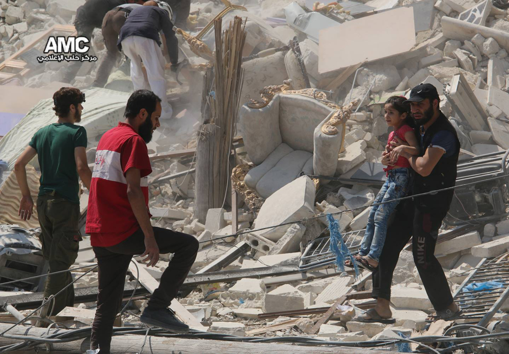 A Syrian man carries a girl away from a destroyed building after barrel bombs were dropped on Aleppo's Bab al-Nairab neighborhood on Saturday.