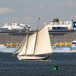 A schooner sailing near Peaks Island is dwarfed by Royal Caribbean's Anthem of the Seas, which is docked Sunday on the other side of Portland Harbor.