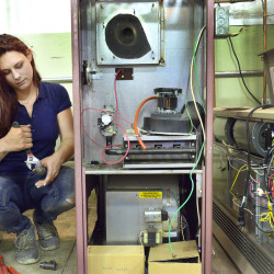 Sara Myers works on the piping of a gas furnace she's assembling at the Technical Education Center in Brunswick. Myers, 22, was working at a day care facility when she decided to enroll. She graduates in two weeks and already has job interviews lined up.