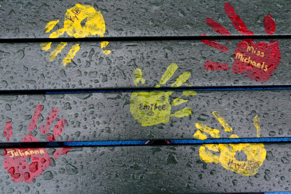 Painted hand prints with names of teachers and students are on a playground bench at the new Sandy Hook Elementary School in Newtown, Conn., seen here in July. The names on the bench are not those of people killed in the 2012 massacre at the school.