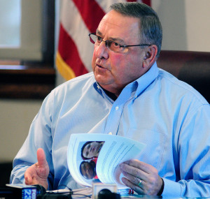 Gov. Paul LePage flips through a three-ring binder of news releases and articles about drug arrests during a meeting with reporters on Friday at the State House. Joe Phelan/Kennebec Journal