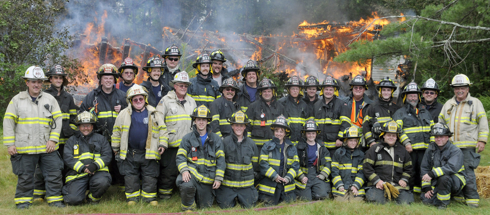 Members of the Monmouth Fire Department pose Sunday at a home they burned during a training exercise.