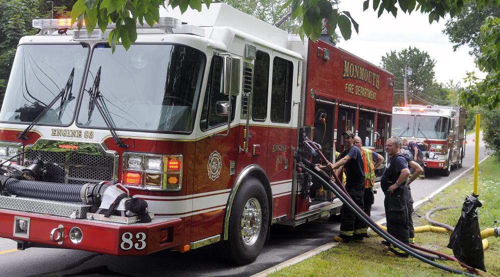 Monmouth Fire Department members draw water from the company's new rescue pumper Sunday while suppressing the controlled burn of a home in town during a training exercise. The volunteer company practiced interior fire suppression while using its two new fire engines, according to Chief Dan Roy.