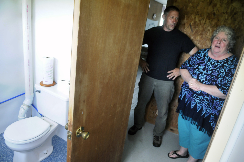 Dana and Debbie Rogers show off the new flushing toilet Tuesday at the Arlington Grange in Whitefield.