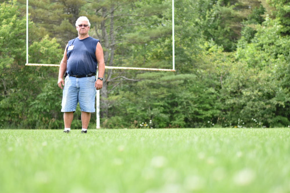 Jeff Sheive, facilities director at Oakland-based Regional School Unit 18, stands on a football field behind Messalonskee Middle School, one of the fields where the district is testing the strategy of overseeding as part of a U.S. Department of Agriculture-funded research project on improving school turf.