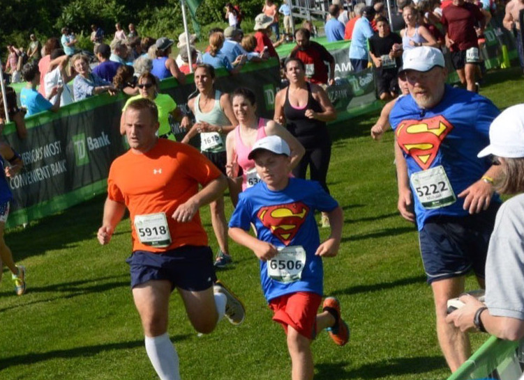 Mike Gammon, wearing bib No. 5222, and his son, Isaac, center, both of Randolph, cross the finish line at the 2015 TD Beach To Beacon 10K. The father-son duo are running in their second consecutive B2B together on Saturday.