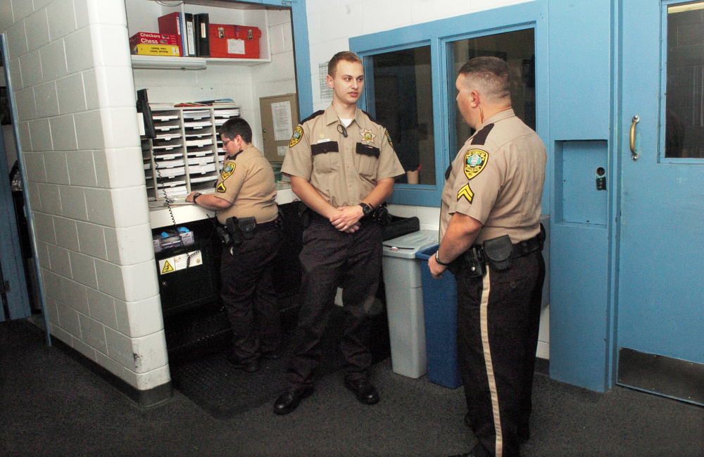 """Thomas College student and Kennebec County Correctional Facility intern Tyler LeClair, center, speaks with Cpl. Sean Cipriano with officer Myra Gagnon behind him at the Augusta jail. LeClair is studying criminal justice and has put some of his """"empathy-based"""" education to the test in his summer job."""