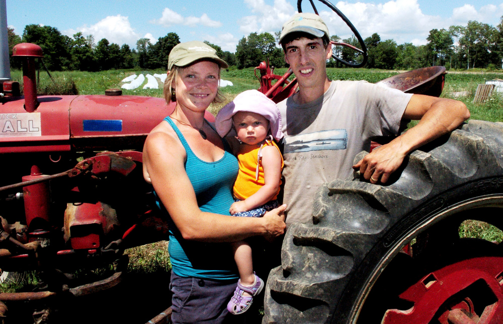 Farmers Johanna Burdet and Jarret Haiss hold their daughter, Tiger, at their Moodytown Gardens farm in Palmyra last week. Younger farmers are part of a growing trend, experts say.