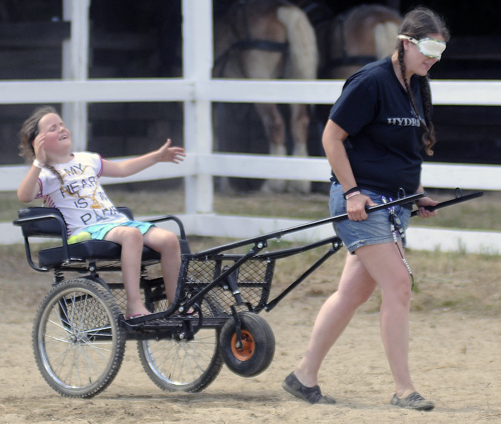 Meka Morrison, 7, reacts to being a little off course while being towed by her mother, Jennifer Morrison, during the Back Seat Driver Contest at the Monmouth Fair on Sunday.