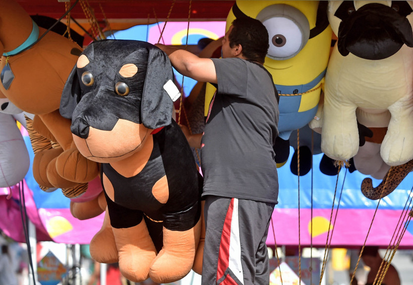 Charles Sanchez, with Fiesta Shows, organizes prizes Tuesday at the Whacky Wire game truck as the company sets up for the 198th annual Skowhegan State fair at the Skowhegan Fairgrounds. Smokey's Greater Shows provides some of the rides on the midway, which is run by Fiesta Shows.