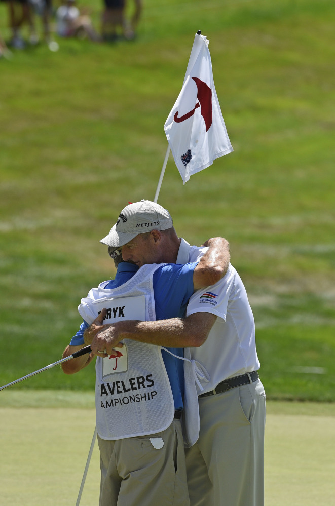Jim Furyk celebrates with his caddy Mike 'Fluff' Cowan after shooting a PGA record 58 during the final round of the Travelers Championship in Cromwell, Connecitcut on Sunday.