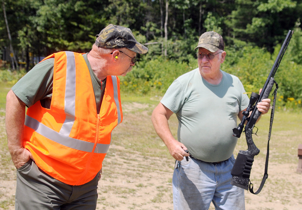 Craig Gerry, range grant coordinator for the Department of Inland Fisheries and Wildlife, right, examines a black powder gun that Dick Salmonson, of Vassalboro, fired Thursday at the IF&W range in Augusta.
