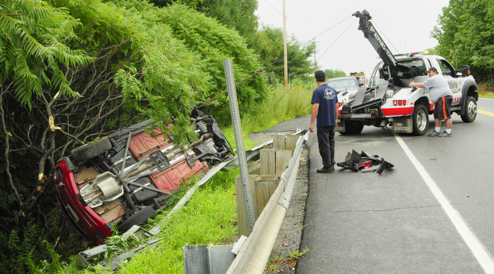 Tow truck operators pull a vehicle out of the ditch Saturday on Route 3 in South China.