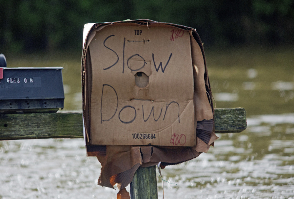 A sign tells motorists to slow down to avoid pushing water into homes near Holden, La.