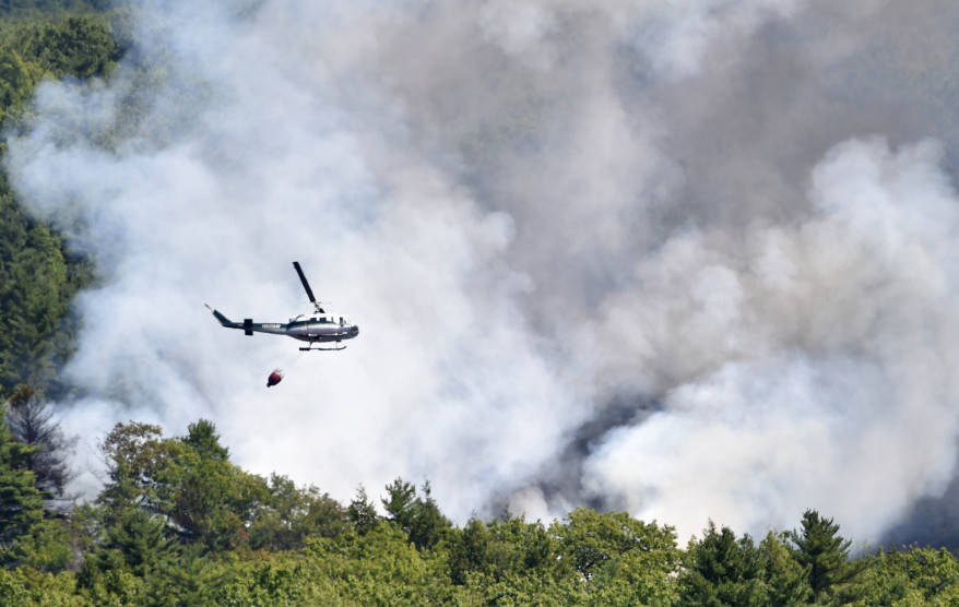 A forest service helicopter attacks a wildfire near Mud Pond on the China-Winslow border last Tuesday. The hot spots from the fire are finally out after flaring for a few days afterwards. Officials are looking for information about how the fire started, including anyone trespassing in the area that day.
