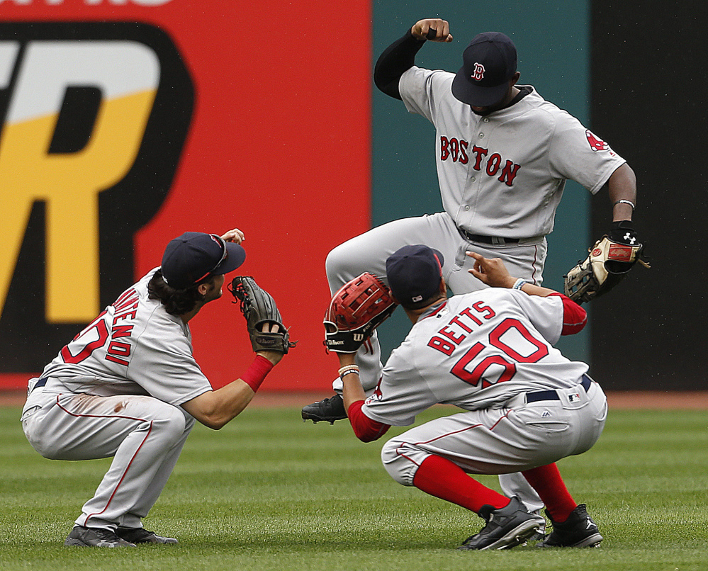 Boston outfielders, from left, Andrew Benintendi, Mookie Betts and Jackie Bradley Jr. celebrate a 3-2 win against the Indians on Monday.
