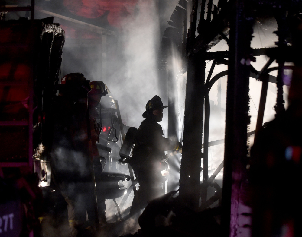 Waterville firefighters battle a Belmont Avenue fire last Wednesday. Investigators said Monday that the fire, which destroyed a garage and several vehicles, was found to have been set intentionally.