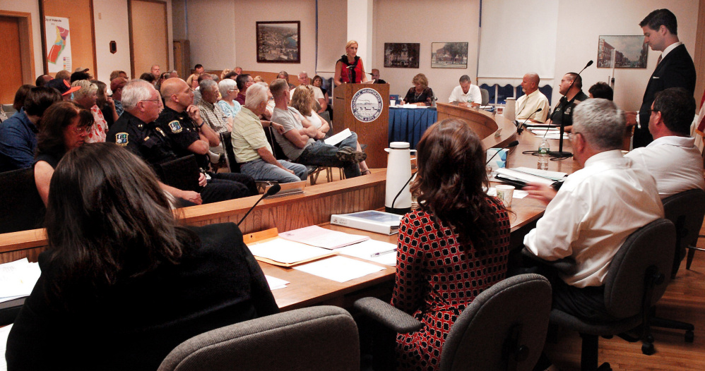 Waterville resident Jessica Laliberte, center, expresses her opinions on the municipal and school budgets before the city council, Mayor Nick Isgro, standing, and other residents and city officials on Tuesday.