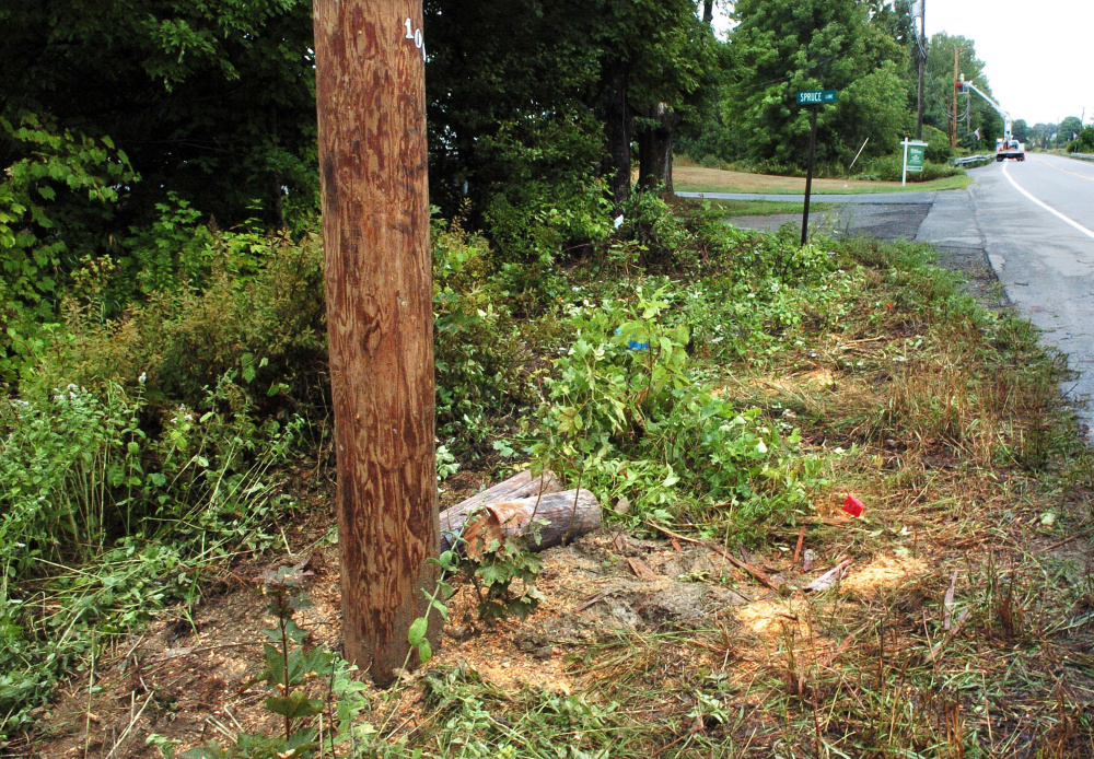 A utility pole on U.S. Route 202 in Unity, foreground, was snapped in half when it was hit by a pickup truck Tuesday night. A utility worker, background, repairs a second pole that he said was also affected by the crash. Harold Fickett III, of Clifton, was killed and the driver and another passenger were injured.